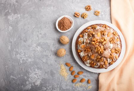 Homemade cake with milk cream, cocoa, almond, hazelnut on a gray concrete  background with orange textile. Top view, flat lay, copy space. Reklamní fotografie