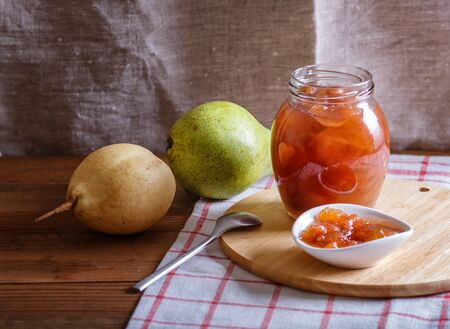 Pear jam in a glass jar on a linen tablecloth on a wooden table. Homemade, copy space. 免版税图像