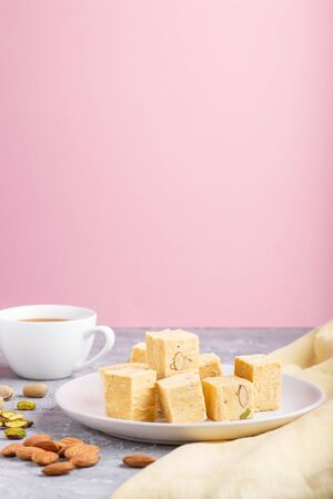 traditional indian candy soan papdi in white plate with almond, pistache and a cup of coffee on a gray and pink background with yellow textile. side view, close up, selective focus. Banque d'images