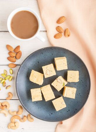 traditional indian candy soan papdi in a blue ceramic plate with almond, pistache, cashew and a cup of coffee on a white wooden background with orange textile. top view, flat lay, close up.
