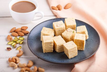 traditional indian candy soan papdi in a blue ceramic plate with almond, pistache, cashew and a cup of coffee on a white wooden background with orange textile. side view, close up, selective focus.