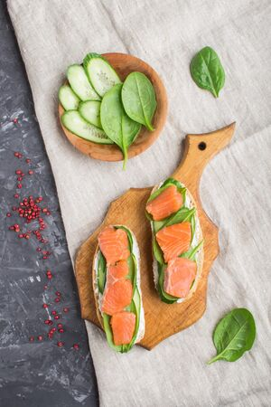 Smoked salmon sandwiches with cucumber and spinach on wooden board on a black concrete background. top view, flat lay. Stok Fotoğraf