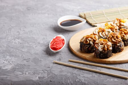 Japanese maki sushi rolls with cream cheese, chopsticks, soy sauce and marinated ginger on wooden board on a gray concrete background. Side view, copy space, selective focus.