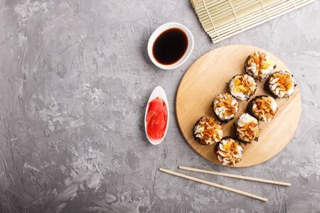 Japanese maki sushi rolls with cream cheese, chopsticks, soy sauce and marinated ginger on wooden board on a gray concrete background. Top view, flat lay, copy space.