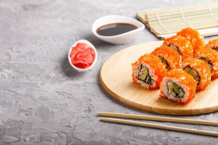Japanese maki sushi rolls with flying fish roe, chopsticks, soy sauce and marinated ginger on wooden board on a gray concrete background. Side view, copy space, selective focus