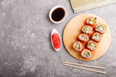 Japanese maki sushi rolls with flying fish roe, chopsticks, soy sauce and marinated ginger on wooden board on a gray concrete background. Top view, flat lay, copy space. 写真素材