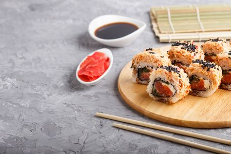 Japanese maki sushi rolls with salmon, sesame, chopsticks, soy sauce and marinated ginger on wooden board on a gray concrete background. Side view, copy space, selective focus.