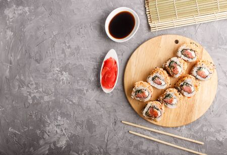 Japanese maki sushi rolls with salmon, sesame, chopsticks, soy sauce and marinated ginger on wooden board on a gray concrete background. Top view, copy space. 写真素材
