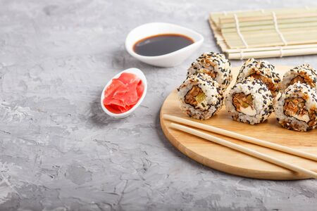 Japanese maki sushi rolls with salmon, sesame, cucumber chopsticks, soy sauce and marinated ginger on wooden board on a gray concrete background. Side view, copy space, selective focus. 写真素材