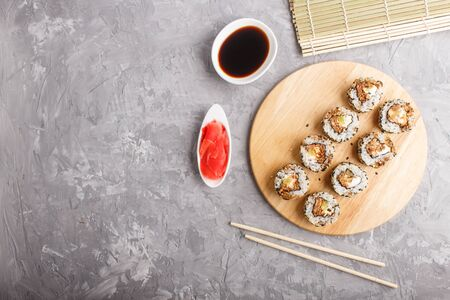 Japanese maki sushi rolls with salmon, sesame, cucumber chopsticks, soy sauce and marinated ginger on wooden board on a gray concrete background. Top view, copy space, flat lay. 写真素材