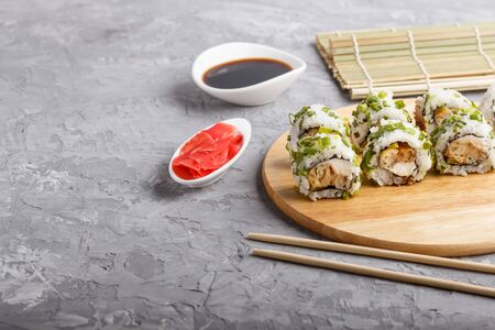 Japanese maki sushi rolls with green onion, chopsticks, soy sauce and marinated ginger on wooden board on a gray concrete background. Side view, copy space, selective focus.