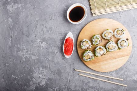 Japanese maki sushi rolls with green onion, chopsticks, soy sauce and marinated ginger on wooden board on a gray concrete background. Top view, copy space, flat lay.