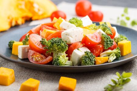 Vegetarian salad with broccoli, tomatoes, feta cheese, and pumpkin on a blue ceramic plate on a black concrete background and linen textile, side view, close up, selective focus. Stok Fotoğraf