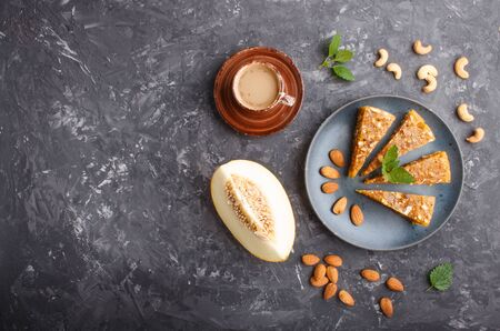 Traditional turkish candy cezerye made from caramelised melon, roasted walnuts, hazelnuts, cashew, pistachios in blue ceramic plate and a cup of coffee on a black concrete background. top view, flat lay, copy space.