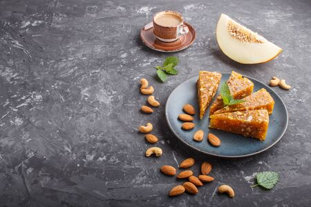 Traditional turkish candy cezerye made from caramelised melon, roasted walnuts, hazelnuts, cashew, pistachios in blue ceramic plate and a cup of coffee on a black concrete background. side view, close up, copy space.