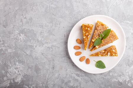 Traditional turkish candy cezerye made from caramelised melon, roasted walnuts, hazelnuts, pistachios on white ceramic plate on a gray concrete background. top view, flat lay, copy space. Stockfoto