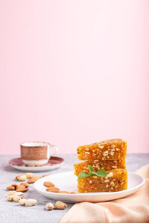Traditional turkish candy cezerye made from caramelised melon, roasted walnuts, hazelnuts, cashew, pistachios on white ceramic plate and a cup of coffee on a gray and pink background. side view, close up. Stockfoto