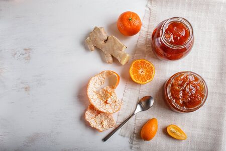 Tangerine and kumquat jam in a glass jar with fresh fruits on white wooden background. Homemade, copy space, top view.