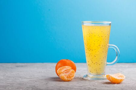 Glass of tangerine orange colored drink with basil seeds on a gray and blue background. Morninig, spring, healthy drink concept. Side view,  copy space.