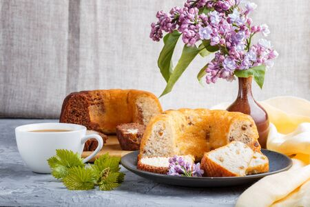 Cakes with raisins and chocolate and a cup of coffee. lilac flowers on a gray concrete
