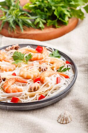 Rice noodles with shrimps or prawns and small octopuses on gray ceramic plate on a white linen textile.
