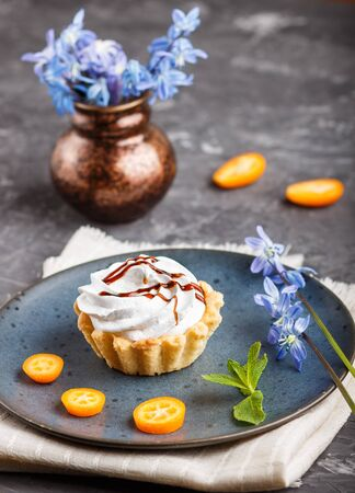 Cake with whipped egg cream on a blue ceramic plate with kumquat slices and mint leaves on a black concrete background with linen napkin. decorated with blue flowers. side view.