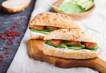Smoked salmon sandwiches with cucumber and spinach on wooden board on a linen background. side view, close up. Stock fotó