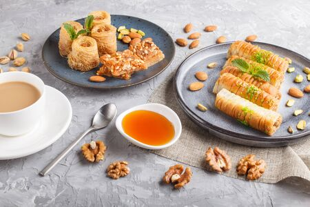 Set of various traditional arabic sweets: baklava, kunafa, basbus in  ceramic plates on a gray concrete background. top view, flat lay. Stock fotó