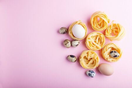 Raw uncooked tagliatelle pasta with quail eggs on a pink pastel background. top view, copy space.