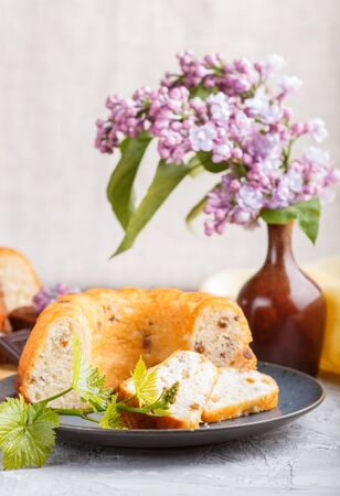 Cakes with raisins and chocolate and a cup of coffee. lilac flowers on a gray concrete background, side view. Stock fotó