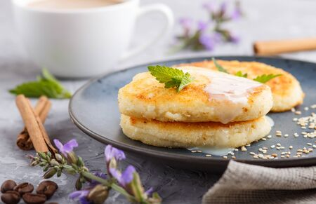 Cheese pancakes on a blue ceramic plate and a cup of coffee on a gray concrete background. side view, close up. Stock fotó