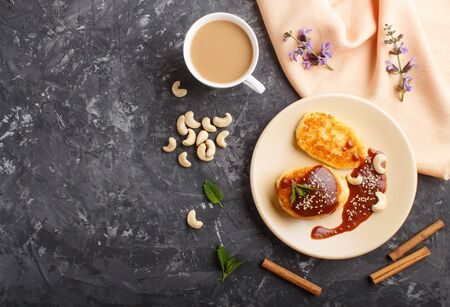 Cheese pancakes with caramel sauce on a beige ceramic plate and a cup of coffee on a black concrete background. top view, flat lay, copy space.