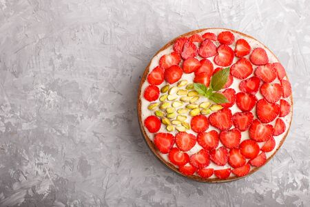 Homemade cake with yoghurt cream, strawberry and pistachio on a gray concrete  background. top view. flat lay, copy space.
