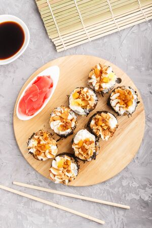 Japanese maki sushi rolls with cream cheese, chopsticks, soy sauce and marinated ginger on wooden board on a gray concrete background. Top view, flat lay, close up.