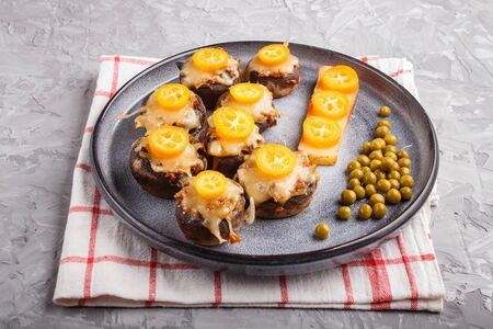 stuffed fried champignons with cheese, kumquats and green peas on a gray concrete background. ceramic plate, side view, close up. Stock fotó