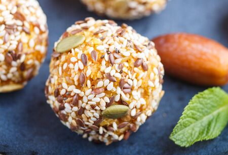 Energy ball cakes with dried apricots, sesame, linen, walnuts and dates with green mint leaves on a blue ceramic plate. side view, close up, macro. vegan homemade candy.
