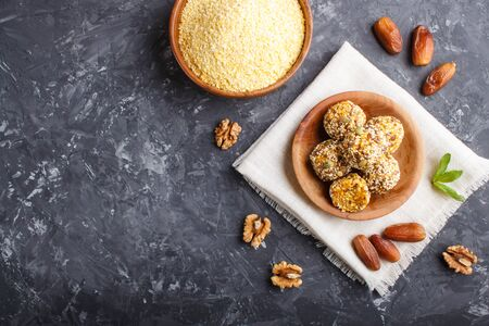 Energy ball cakes with dried apricots, sesame, cornflakes, linen, walnuts and dates with green mint leaves in a wooden bowl on a black concrete  background. linen napkin, top view, copy space, flat lay. vegan homemade candy.