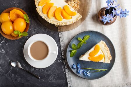 A piece of peach cheesecake on a blue ceramic plate with blue flowers and a cup of coffee on a linen napkin on a black concrete background. top view, close up.