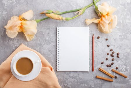 Orange iris flowers and a cup of coffee with notebook on a gray concrete background. Morninig, spring, fashion composition. Flat lay, top view, copy space.