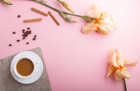 Orange iris flowers and a cup of coffee on pastel pink background. Morninig, spring, fashion composition. Flat lay, top view, copy space.