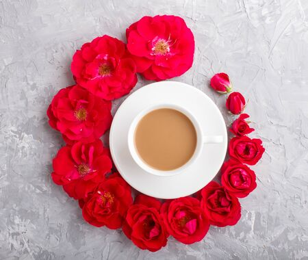Red rose flowers in a spiral and a cup of coffee on a gray concrete background. Morninig, spring, fashion composition. Flat lay, top view, close up.