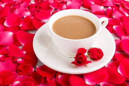 Red rose petals background and a cup of coffee. Morninig, spring, fashion composition. side view, close up.