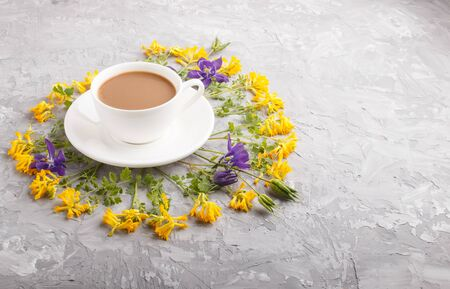 Yellow and blue flowers in a spiral and a cup of coffee on a gray concrete background. Morninig, spring, fashion composition. side view, copy space.