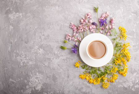 Yellow, pink and blue flowers in a spiral and a cup of coffee on a gray concrete background. Morninig, spring, fashion composition. Flat lay, top view, copy space.