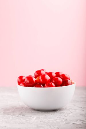 Fresh red sweet cherry in white bowl on gray and pink background. side view, close up, selective focus, copy space.