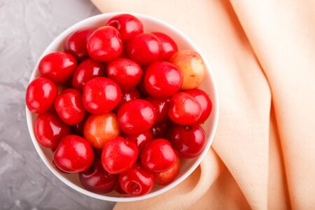 Fresh red sweet cherry in white bowl on gray background with orange textile. top view, flat lay.