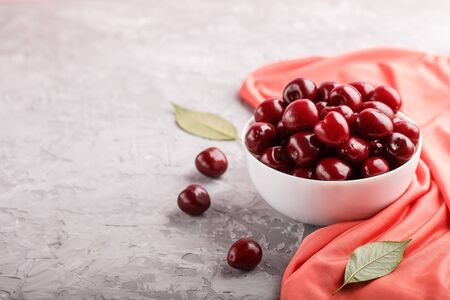 Fresh red sweet cherry in white bowl on gray background with red textile. side view, close up, selective focus, copy space.