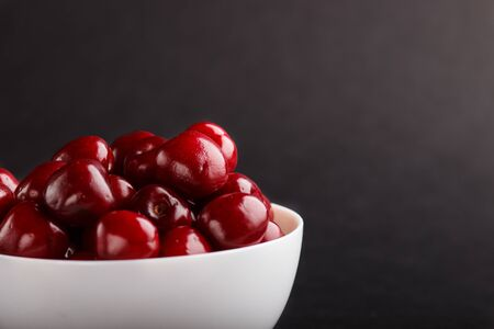 Fresh red sweet cherry in white bowl on black background. side view, copy space, close up.