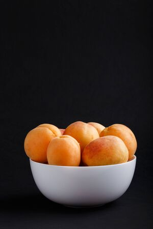 Fresh orange apricots in white bowl on black background. side view, copy space. Stock fotó
