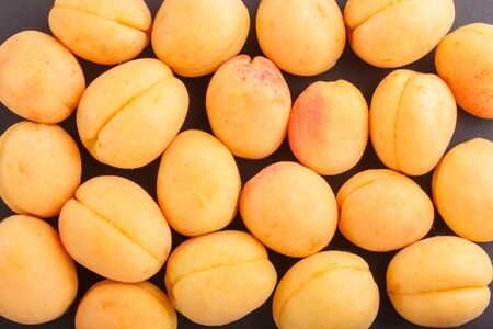 Apricots pattern on black background, top view, flat lay.